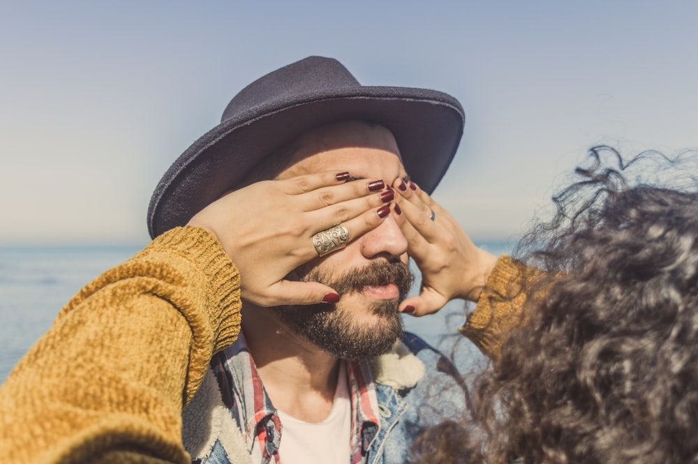 woman covering man's eyes during daytime
