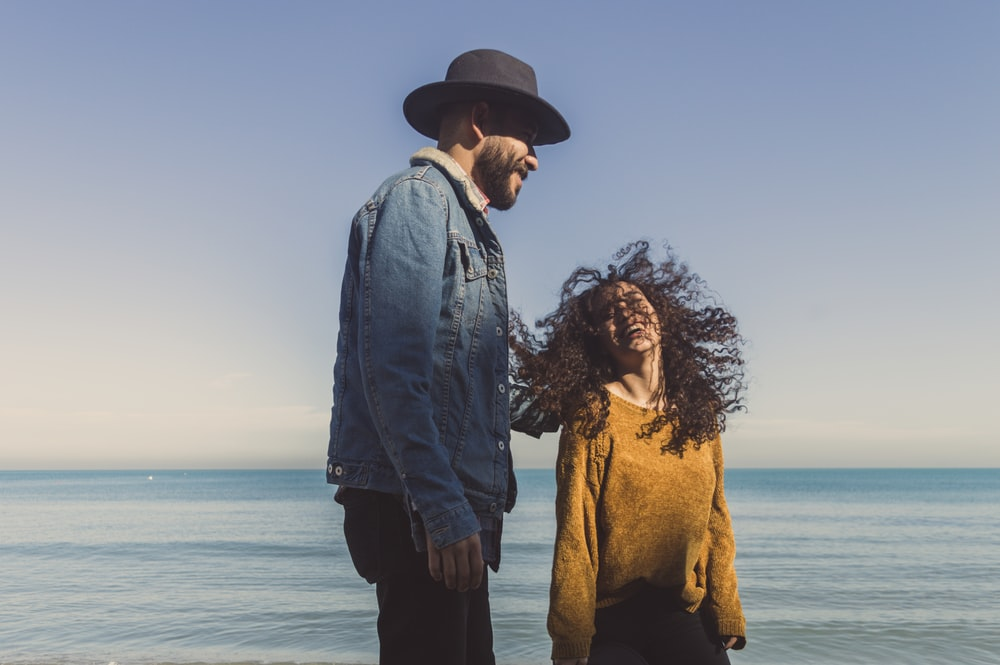 smiling man and woman on seashore