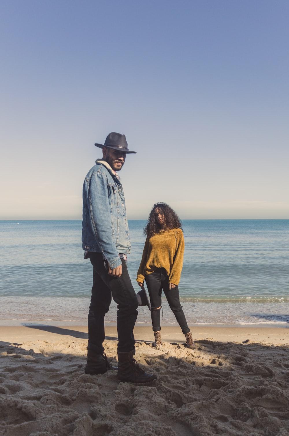 man standing on seashore near woman