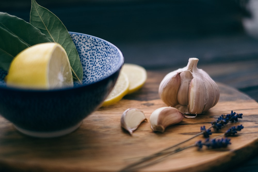 lemon slice and leaves in bowl beside garlic