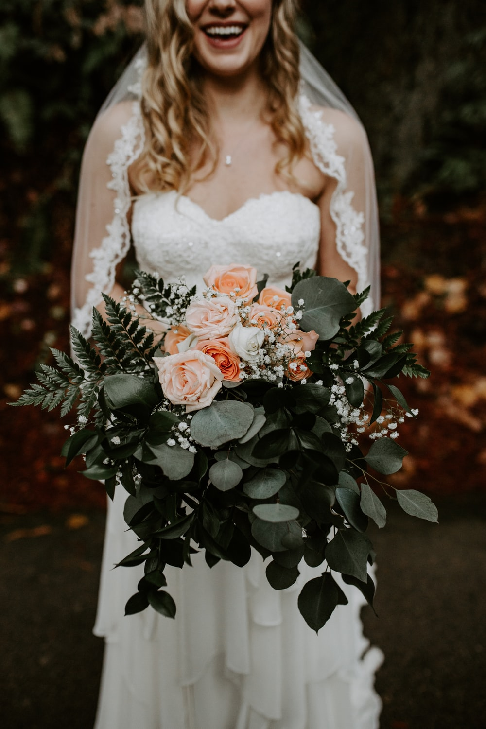 woman wearing wedding gown holding rose bouquet
