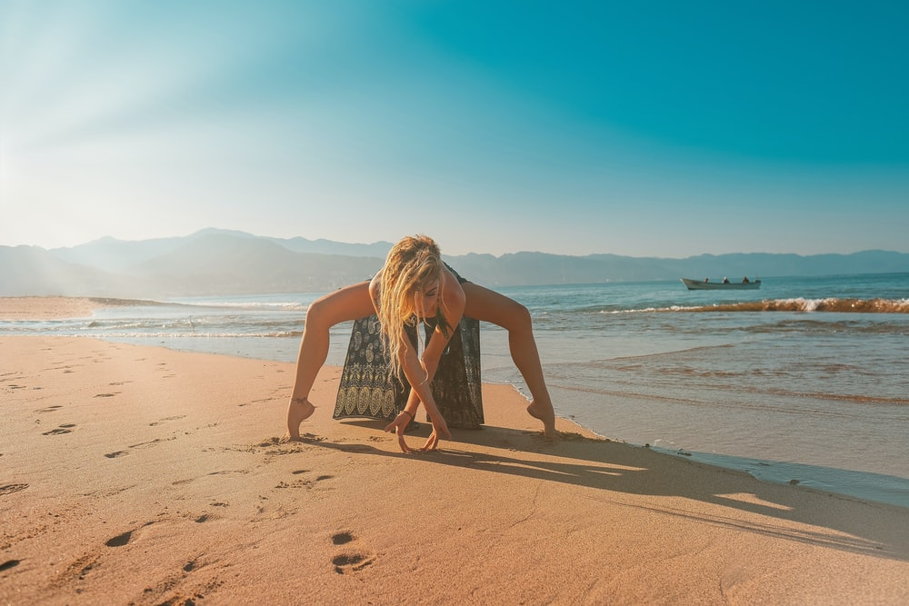 woman posing on sand seashore during day