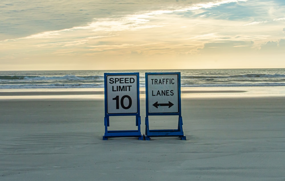 10 speed limit and traffic lanes signs near seashore under white and blue sky