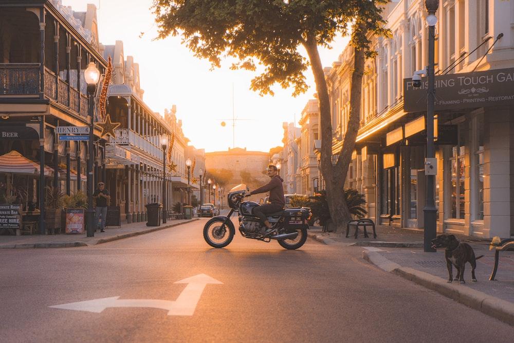 man on standard motorcycle near tree