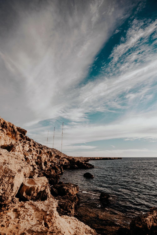 brown rock under white clouds