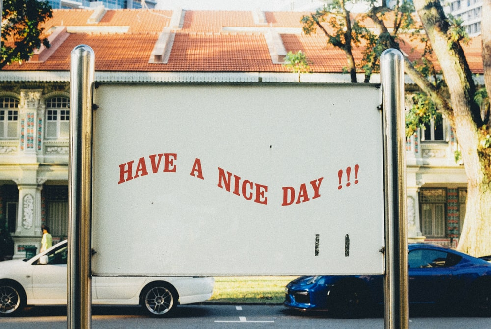 white and blue vehicles on road and have a nice day text on post