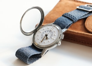 round white analog watch with black band