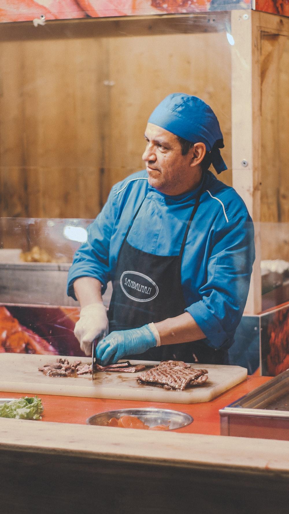 man wearing apron chopping meat