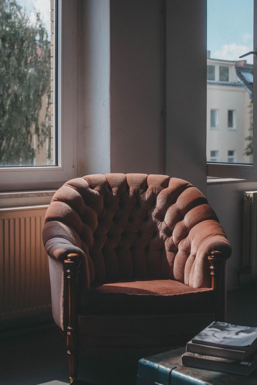 tufted brown suede sofa chair near windows