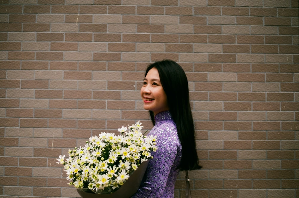 smiling woman holding white petaled flower bouquet