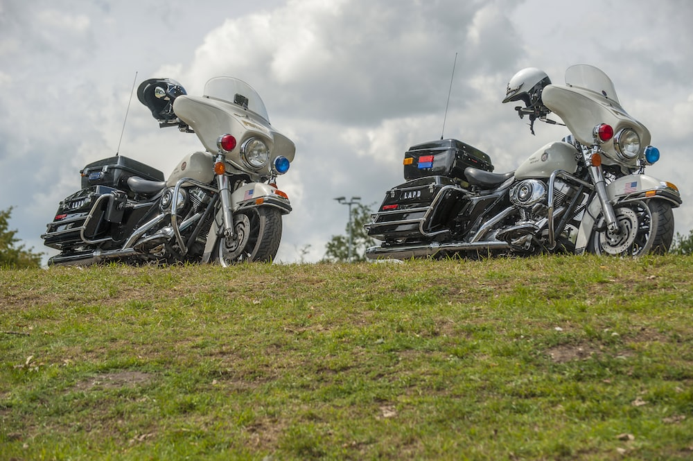 white-and-black touring motorcycles on hill under cloudy sky