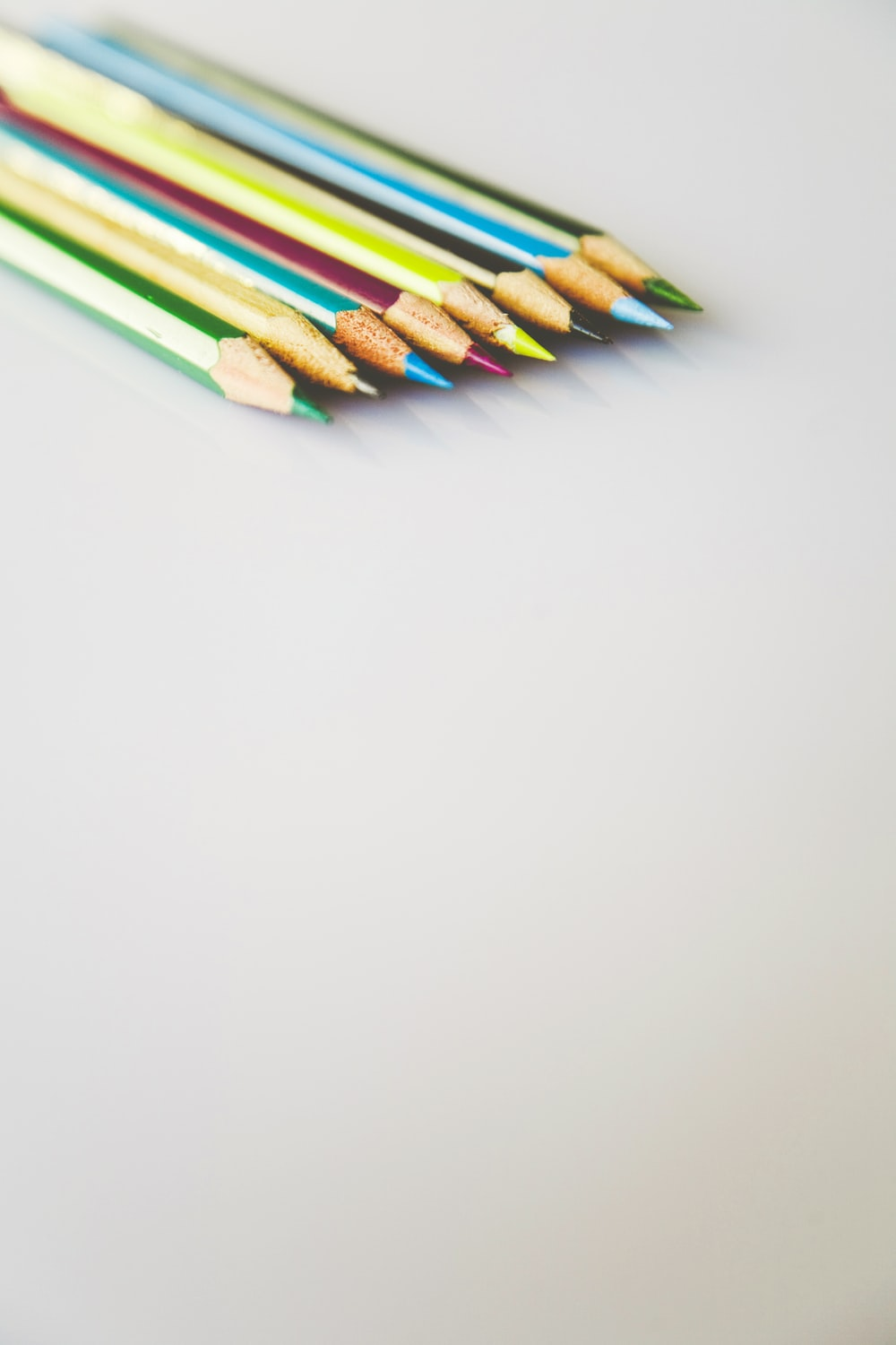 selective focus photography of assorted-color pencils on white surface