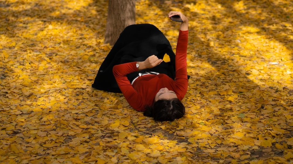woman in red long-sleeved top and black skirt lying on dried leaves