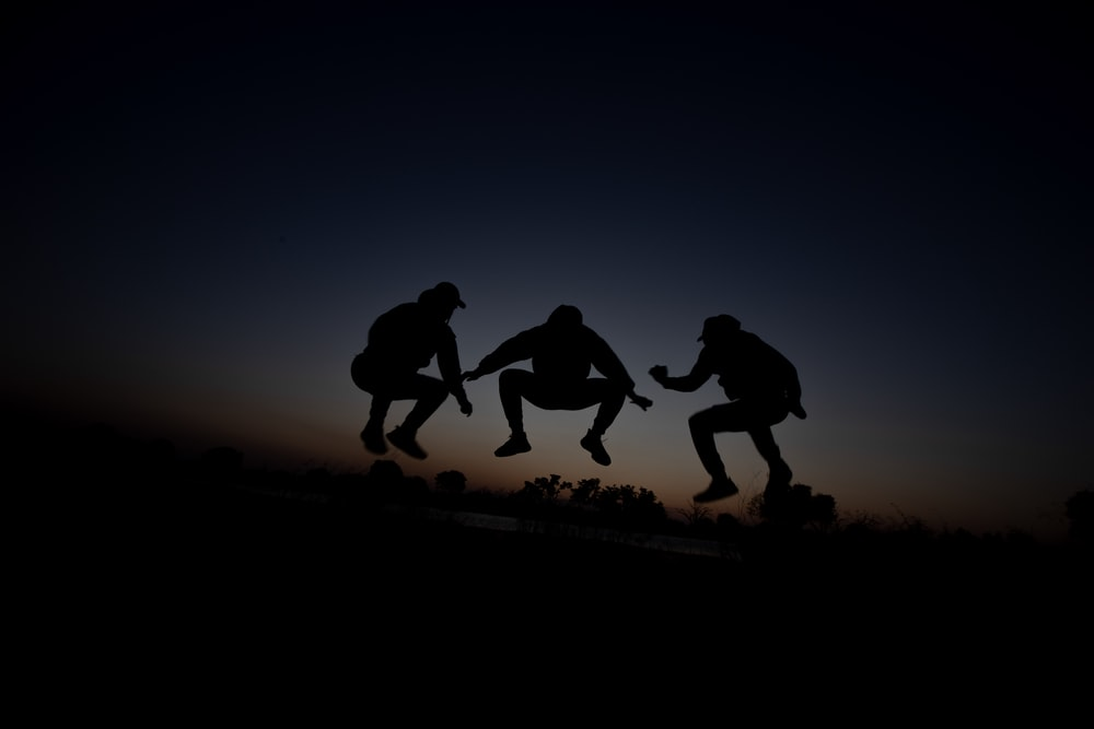 silhouette of 3 person during dawn