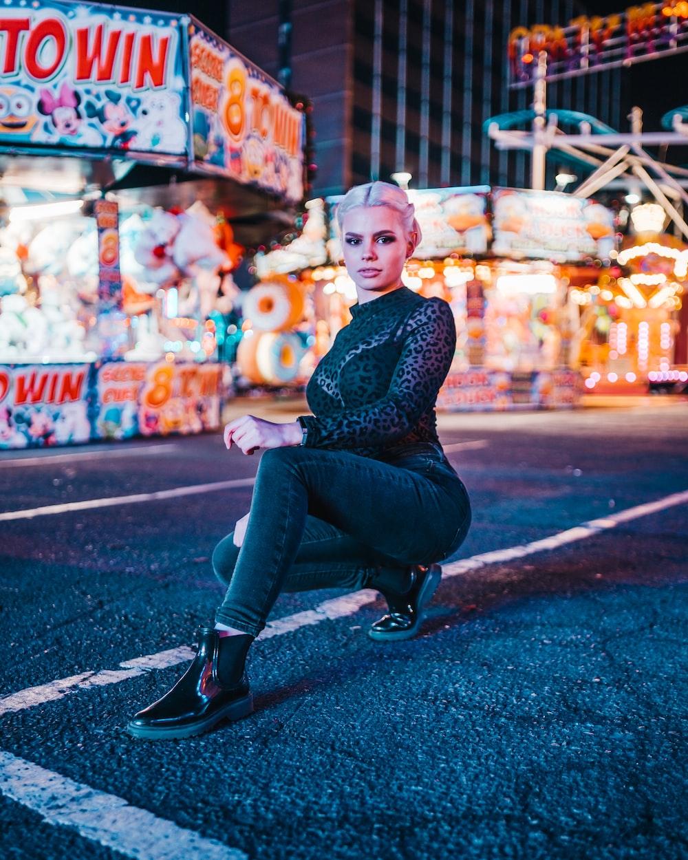 woman sitting on road near amusement park at night