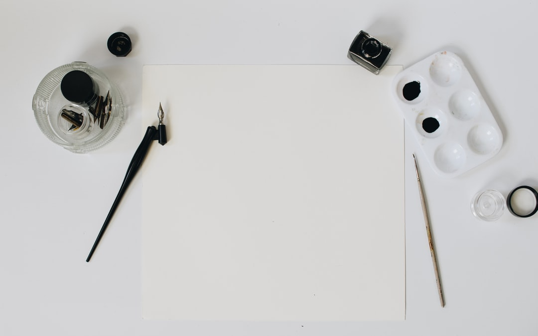 Blank paper with black ink and calligraphy pens and paintbrushes
