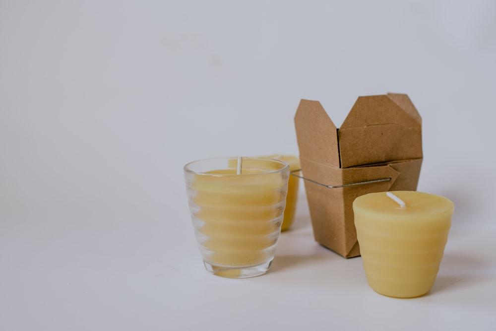 three yellow pillar candles near small brown box