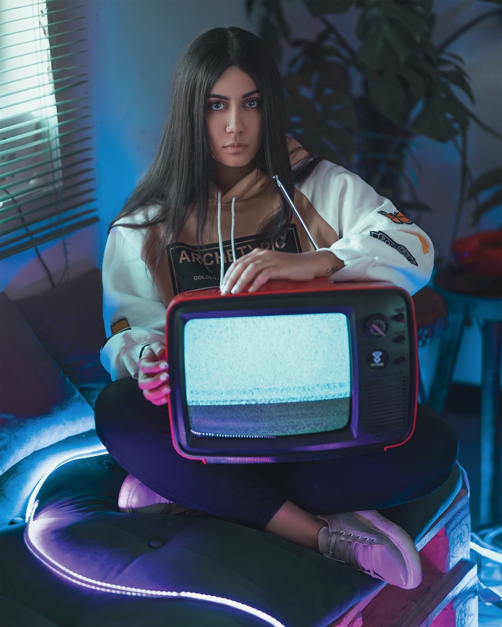 woman wearing pullover hoodie holding red CRT TV