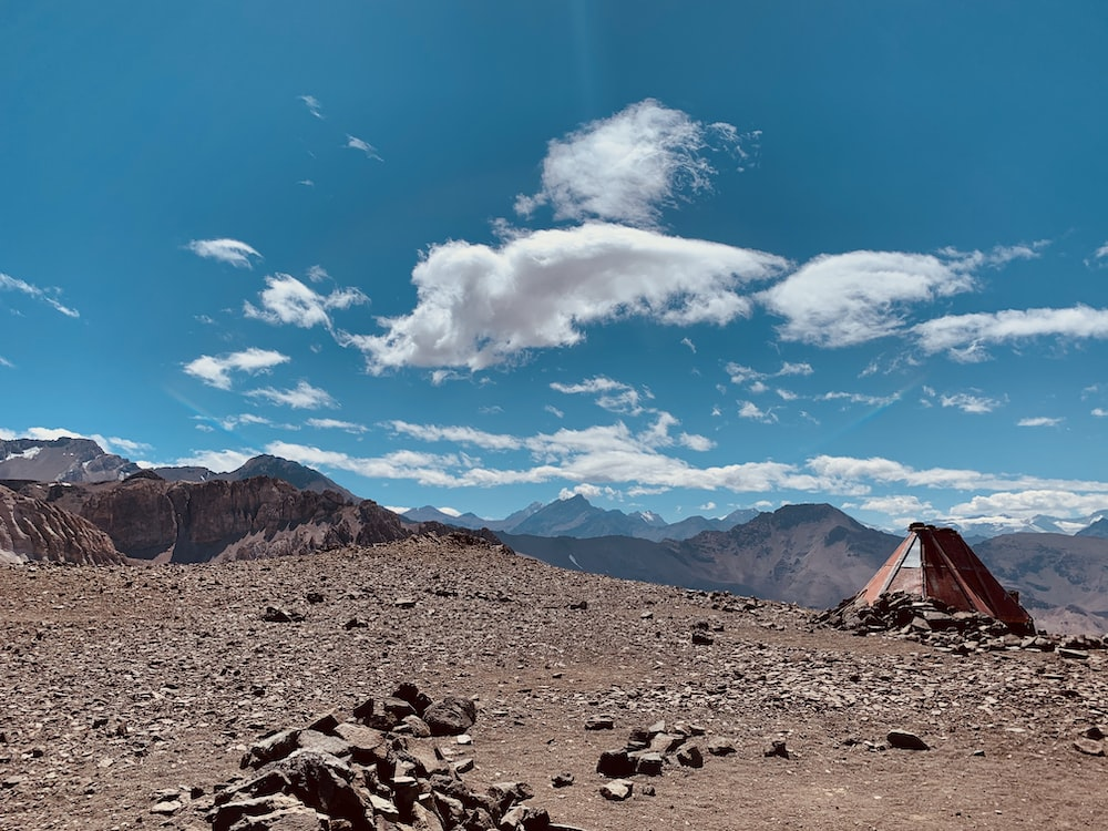 red tent on field viewing mountain under blue and white sky