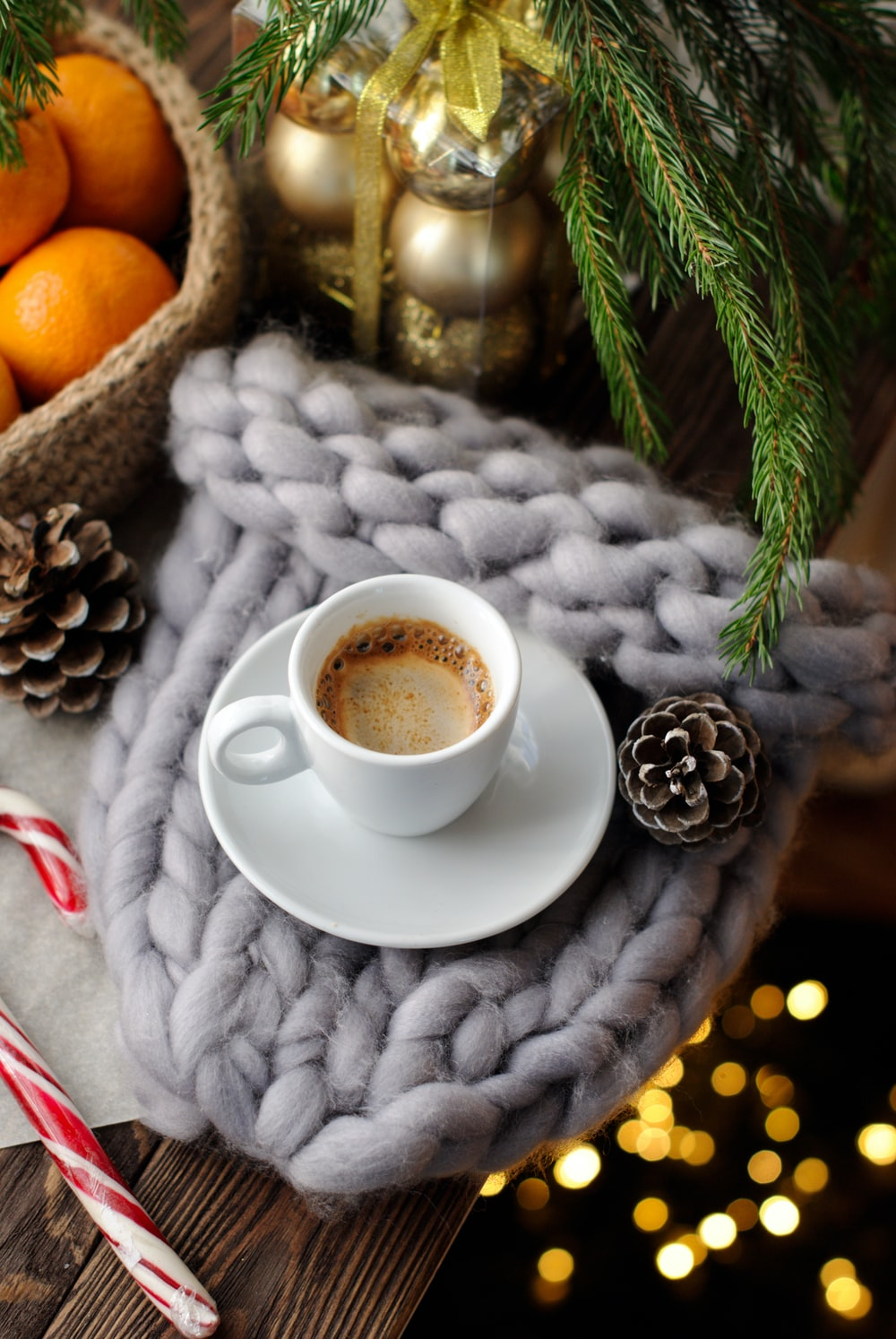 cappuccino on white ceramic mug near brown pinecone, gold baubles, and orange fruits in wicker basket