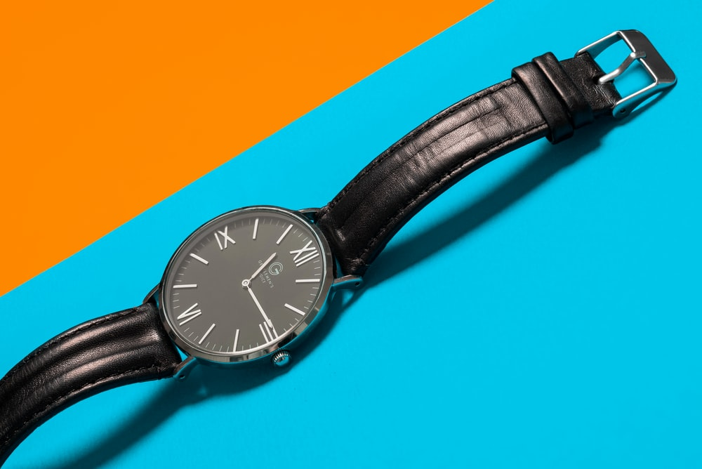 round black analog watch and black leather band