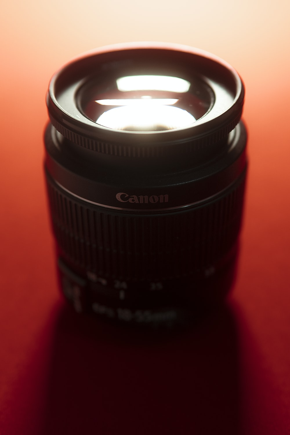 black Canon camera lens on red surface