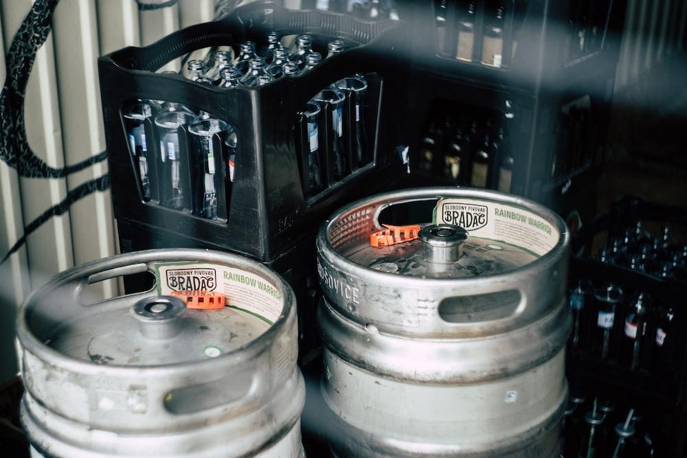 two gray stainless steel beer kegs