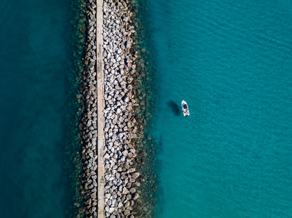 aerial photography of white boat near stone shore during daytime
