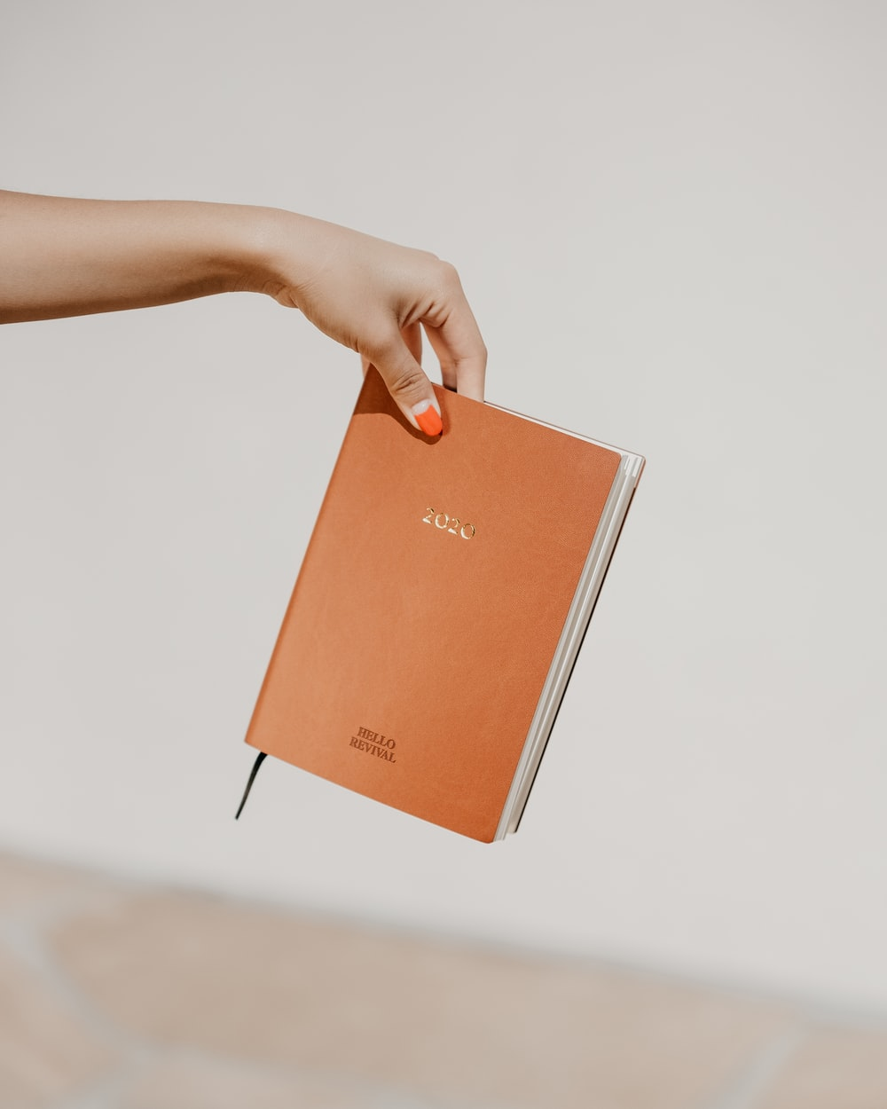 person holding brown book