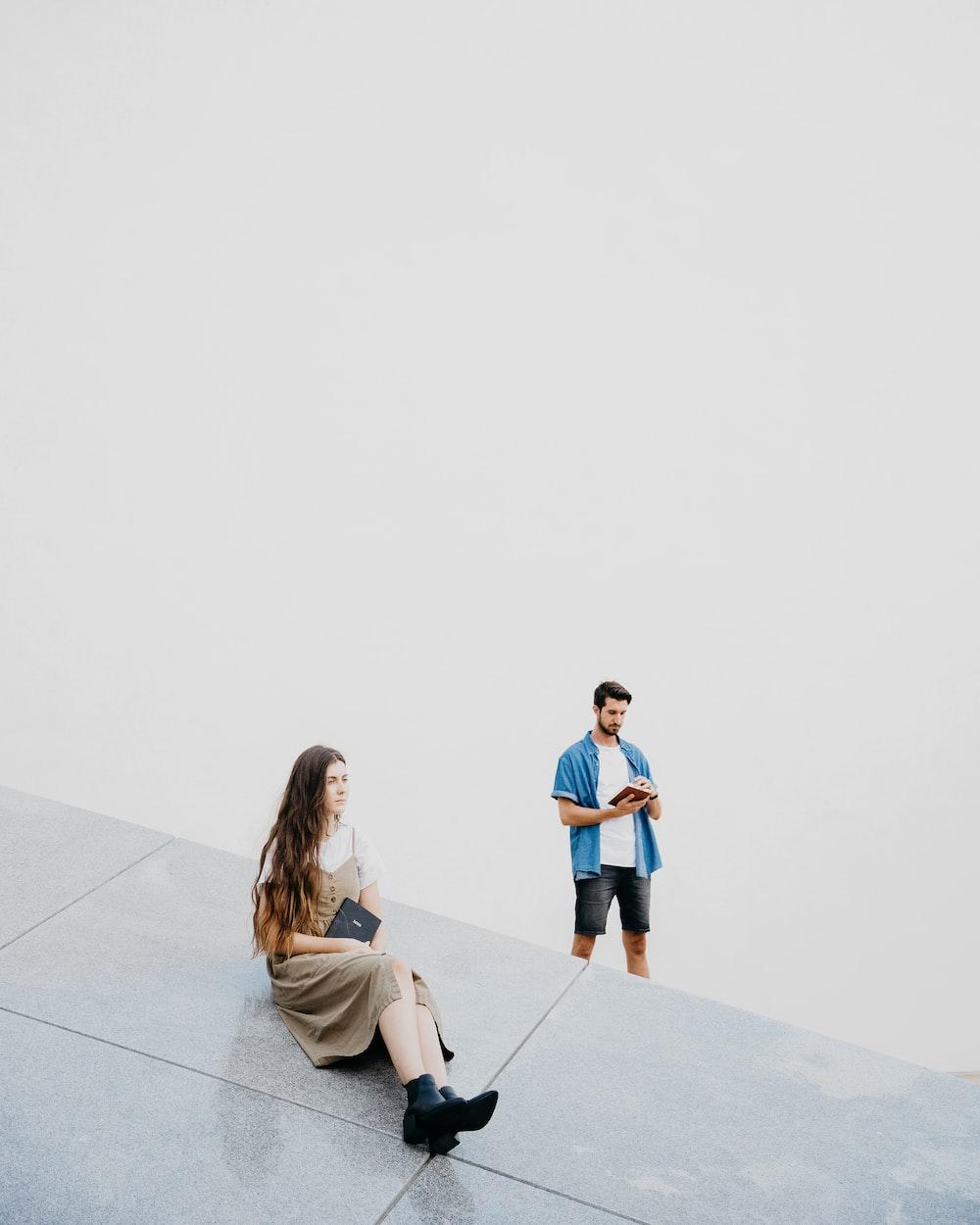woman sitting on floor near man standing