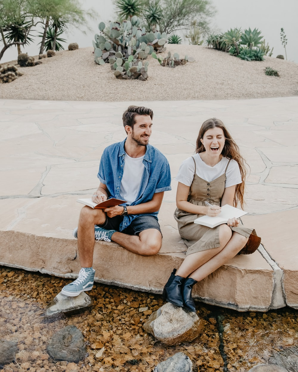 man and woman sitting side by side holding notebooks