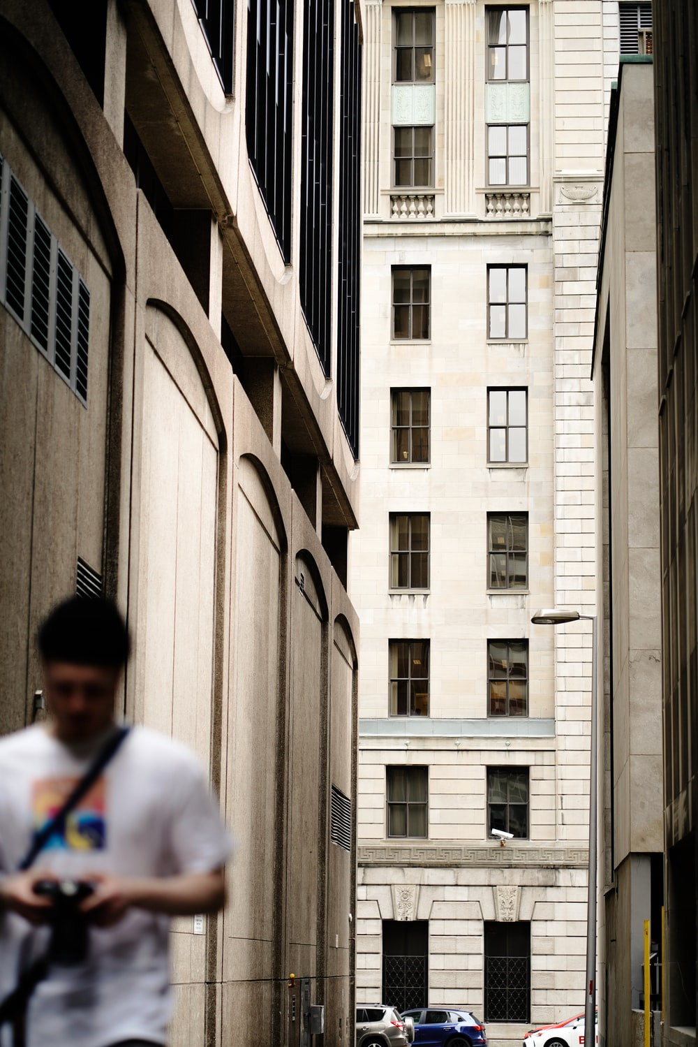 man in white shirt walking beside building