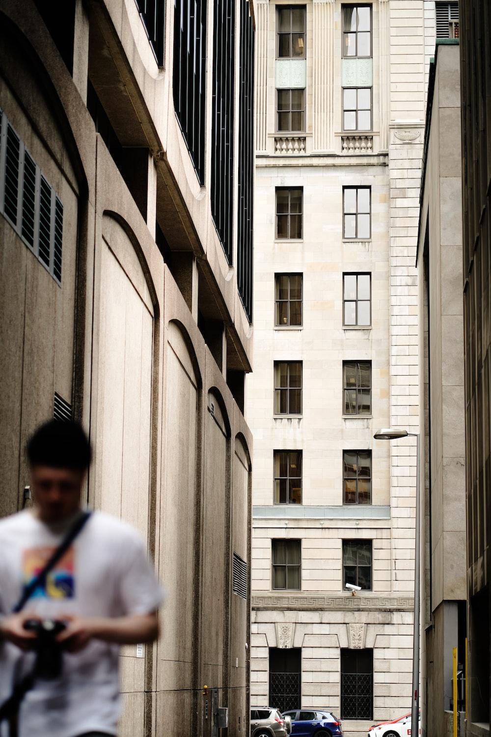 man in white shirt walking beside building