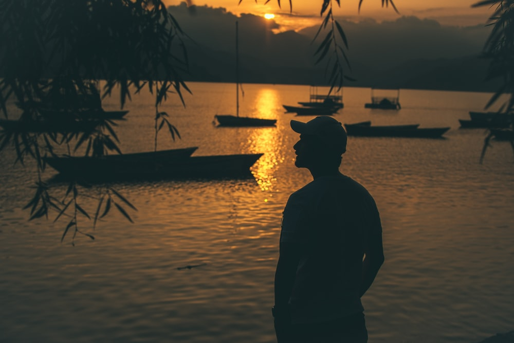 silhouette of person standing near body of water and boats on body of water