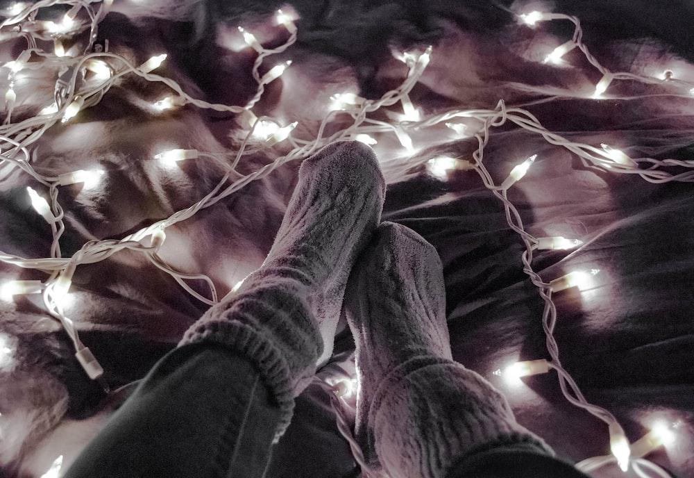 person wearing gray socks near white string lights