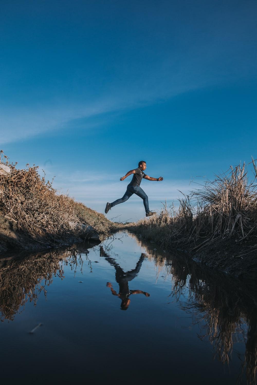 man jumping over stream