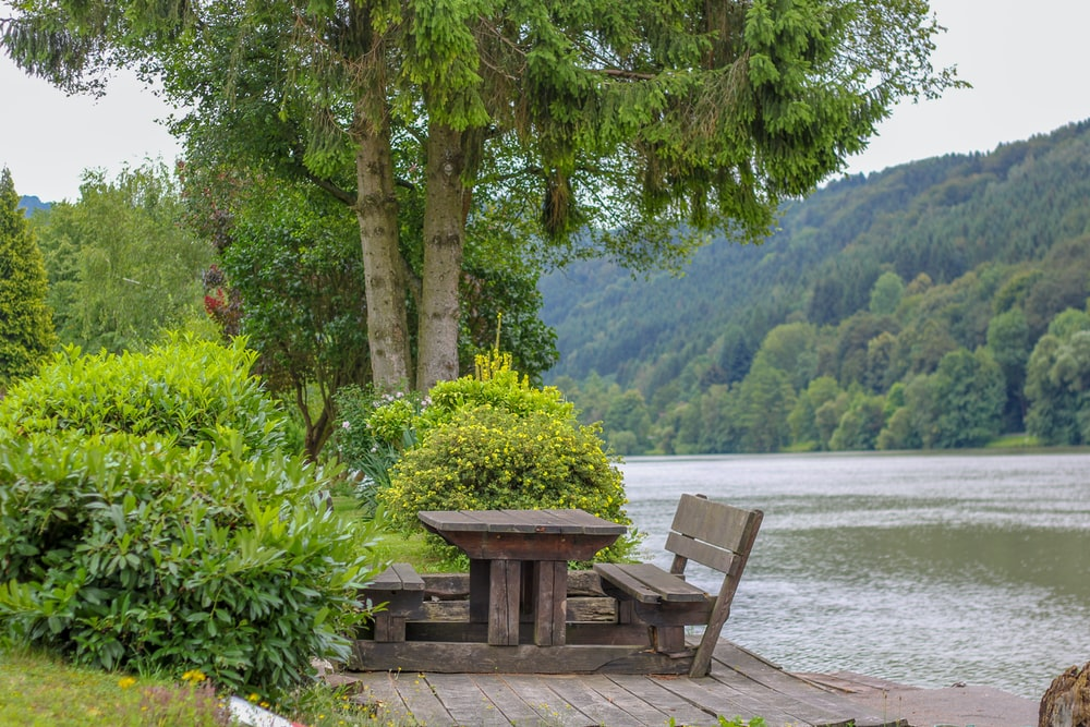 bench and table beside body of water