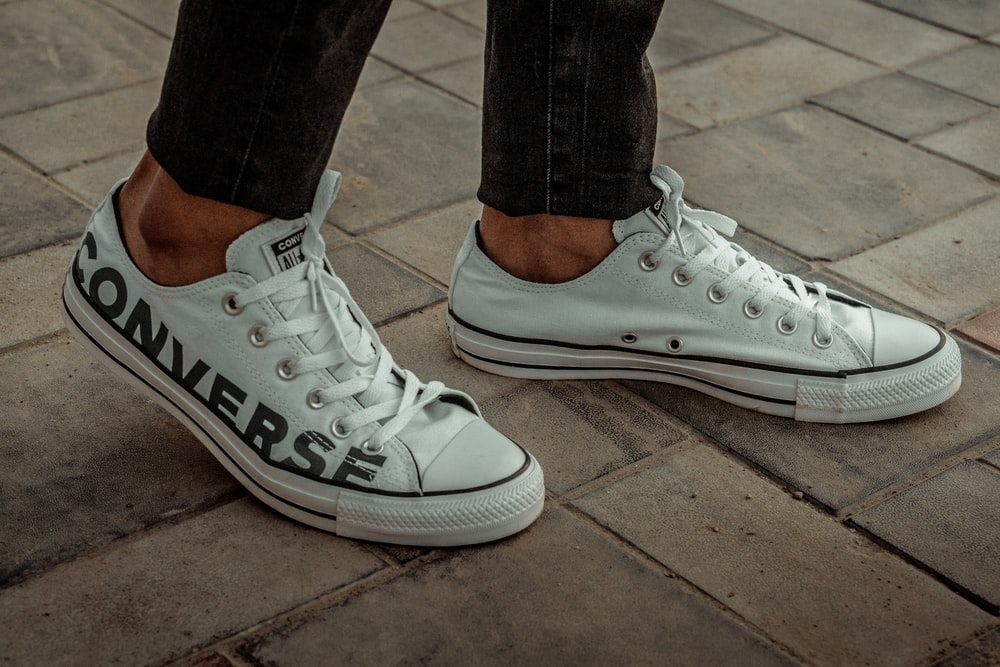 person wearing white Converse low-tops