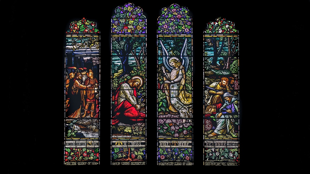 Stained glass windows in the cathedral depicting Jesus, his disciples, and an angel at Gethsemane as the Roman soldiers arrive to arrest him.
