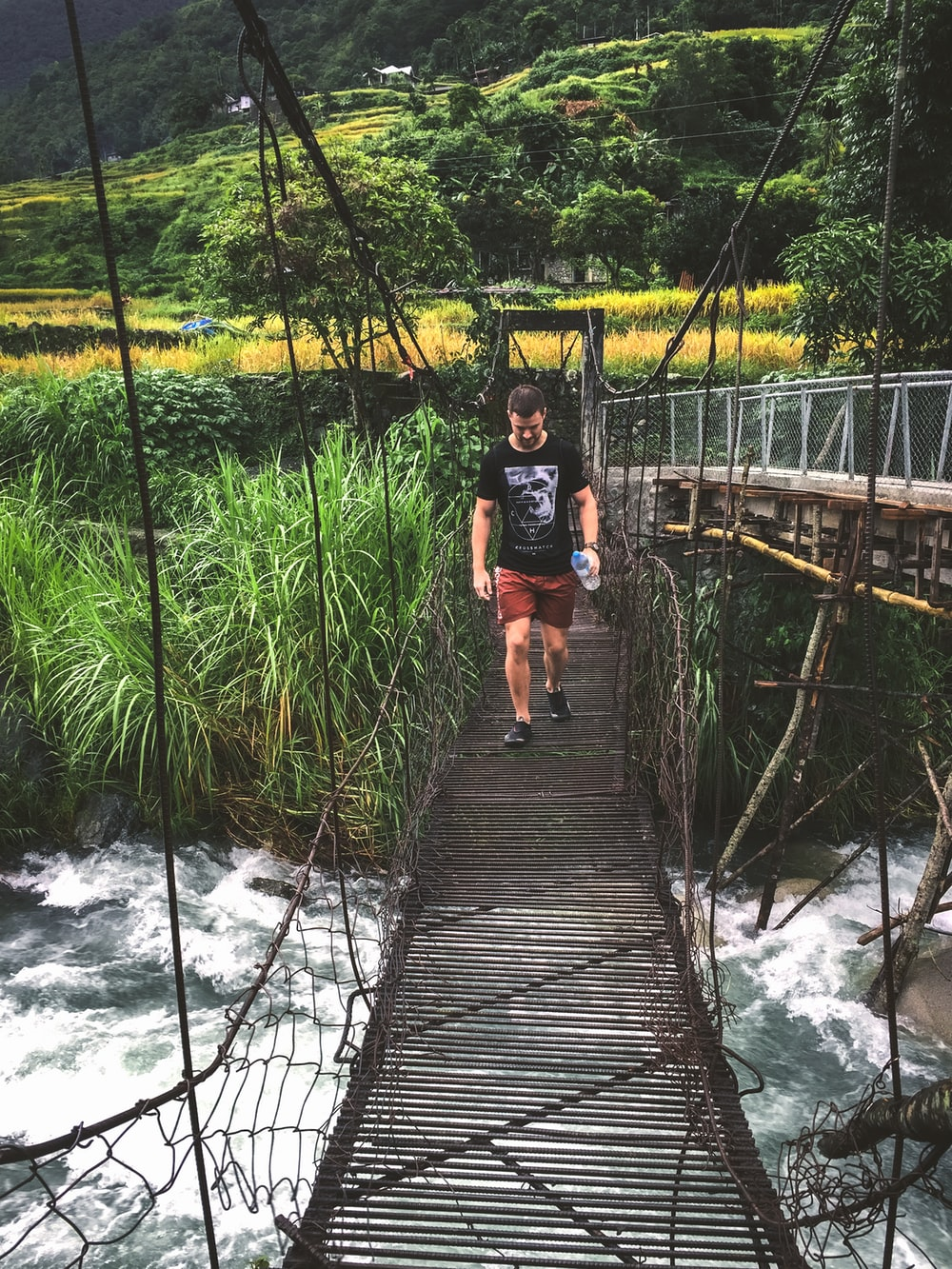 man walking on hanging bridge