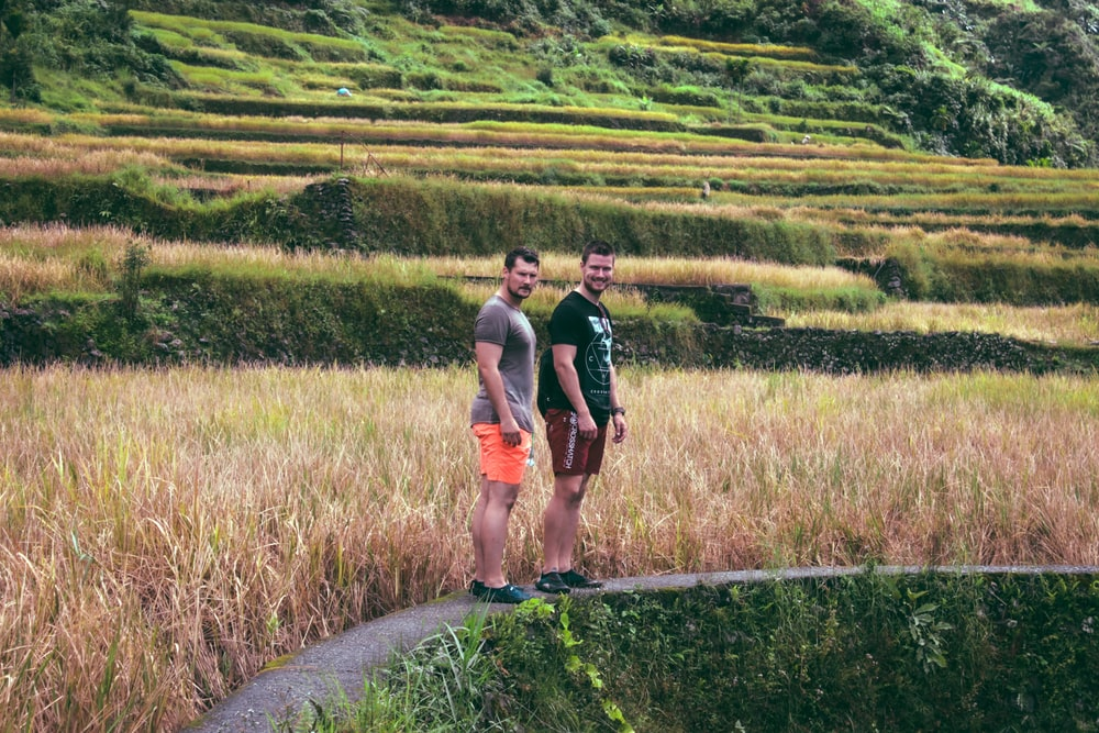 two man standing on pathway near grass and mountain