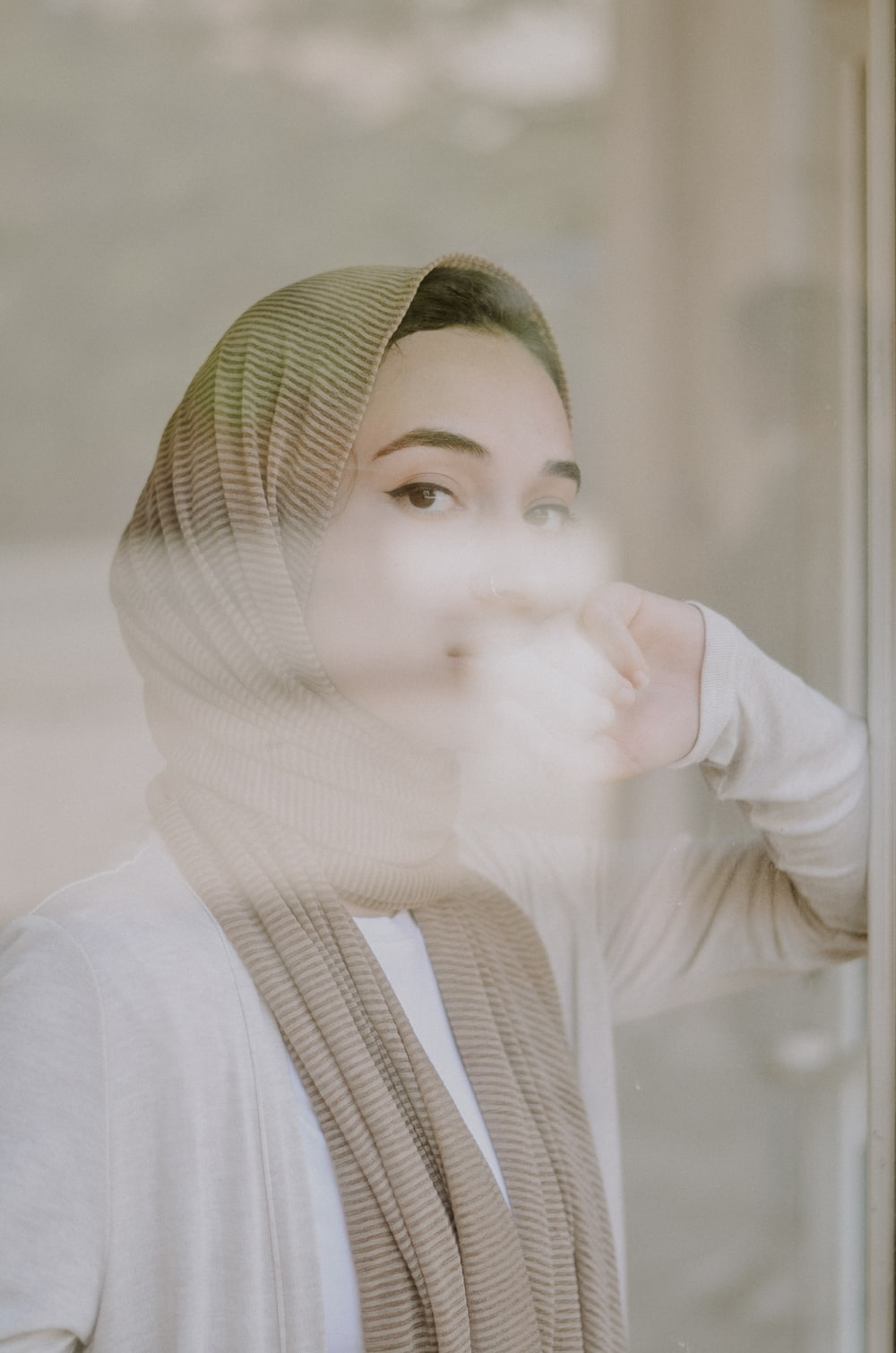 selective focus photography of woman leaning on glass wall