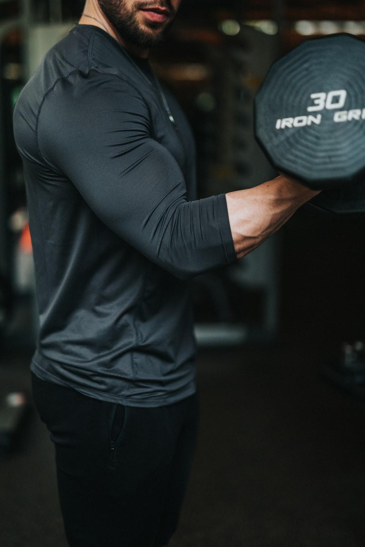 men's black long-sleeved shirt holding dumbbell