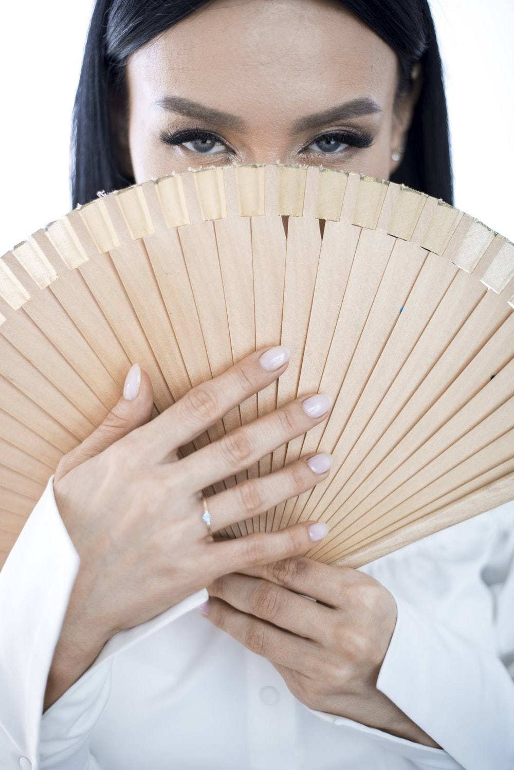 close-up photography of woman holding handfan