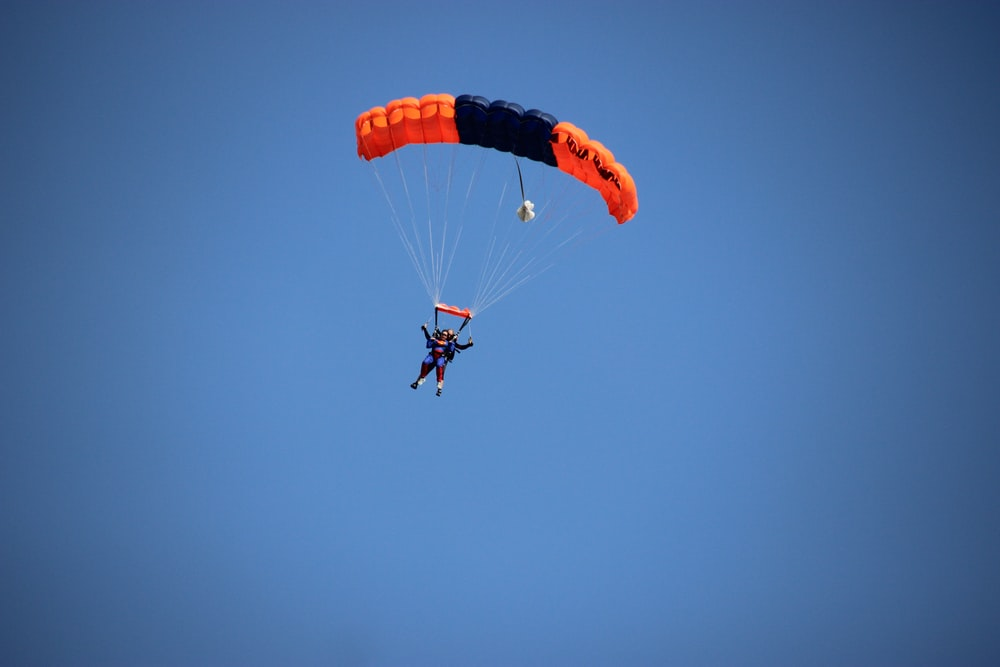 photography of person doing parachute during daytime