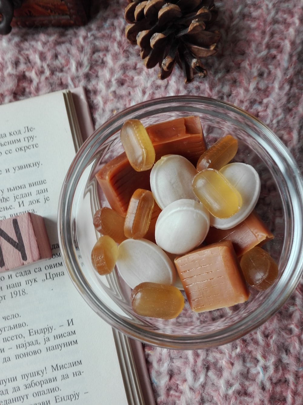 assorted candies in clear glass bowl beside book