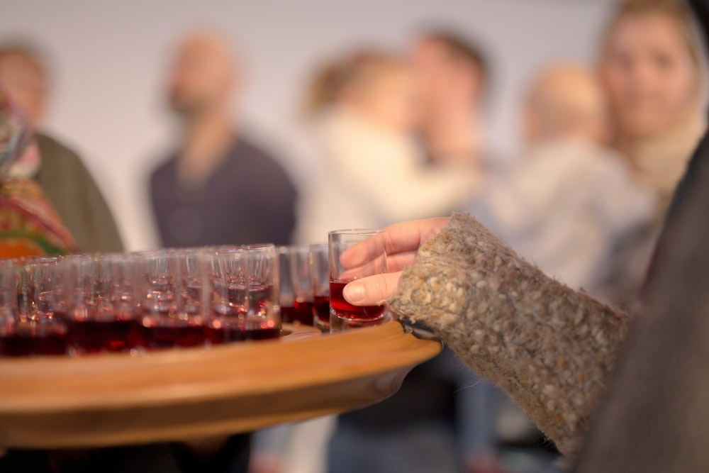 person holding shot glass with red liquid on table top