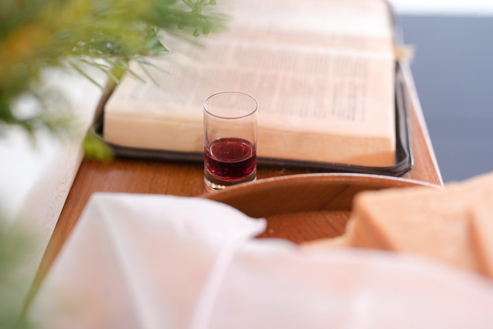 near empty drinking glass beside opened book