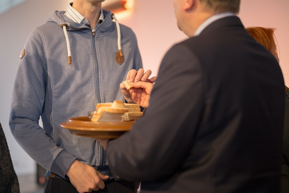 man holding tray with bread in front of man