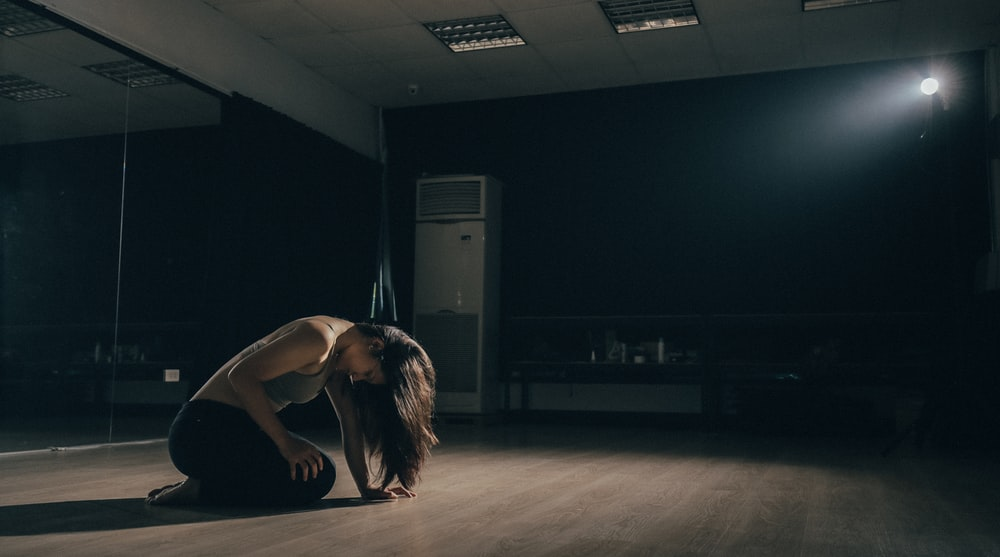 woman kneeling inside room near floor-type AC unit
